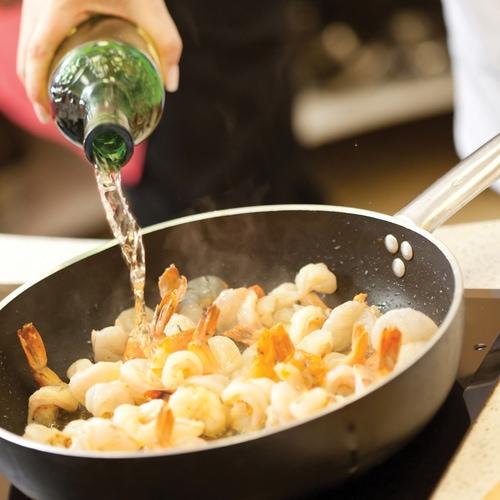 Chef cocinando con vino blanco